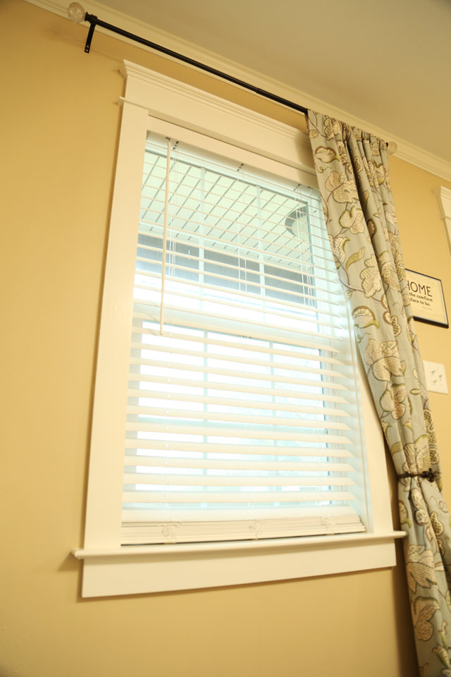 white faux wood blinds hanging in window with craftsman trim