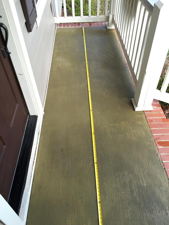 measuring concrete slab porch with yellow tape measure