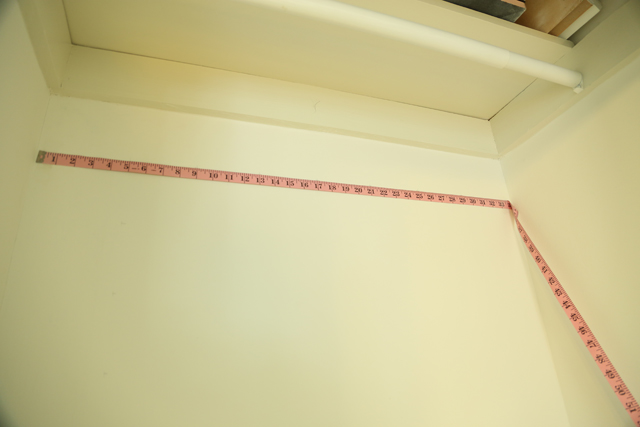 pink sewing measuring tape taped to white closet wall