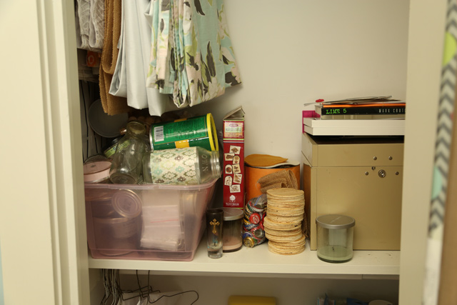 collection of glass jars in pink bin on shelf of white craft closet