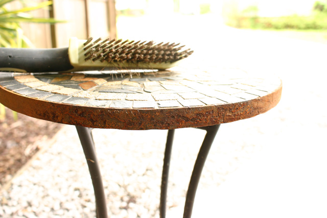 wire brush sitting on rusty plant stand