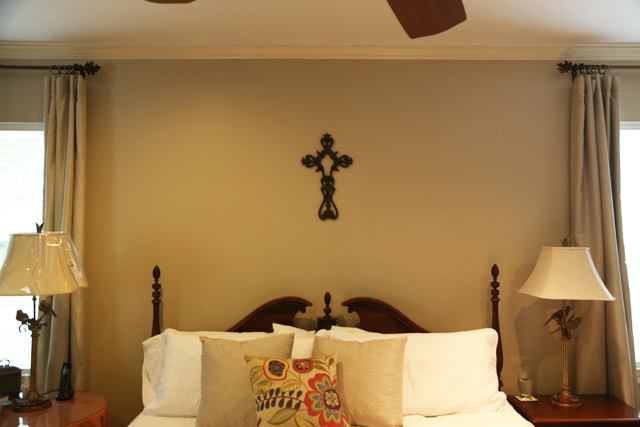 metal cross hung above white king-sized bed