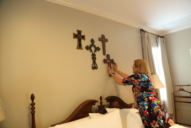 hanging wood and metal crosses on bedroom wall