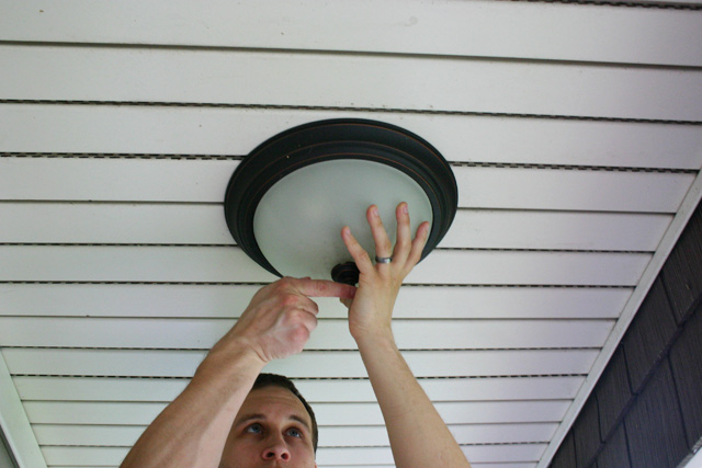 man hands removing flush mount light fixture from white vinyl porch ceiling