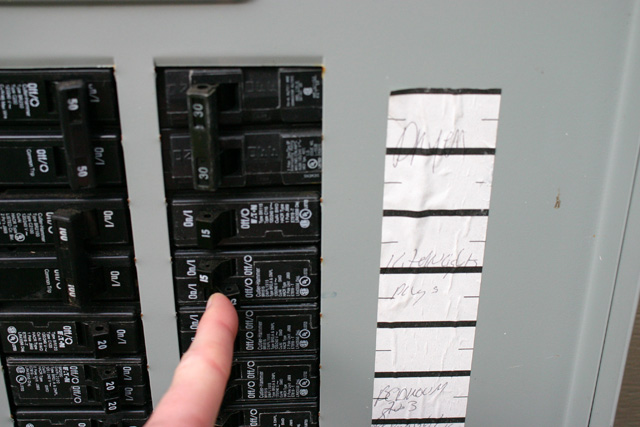 finger flipping breaker in electrical panel box