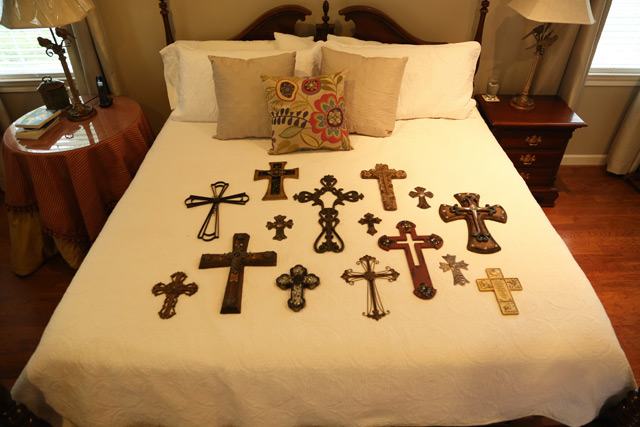metal cross wood crosses laying on king white bed cover