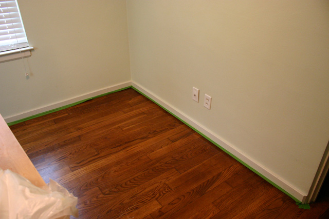 green frogtape painter's tape on shoe molding stained wood floors