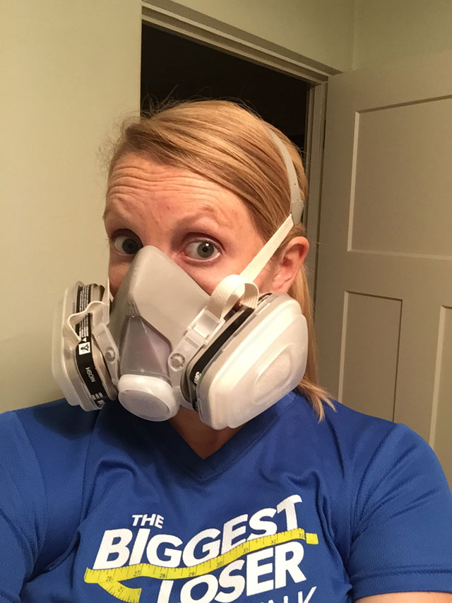 pregnant woman wearing respirator while painting