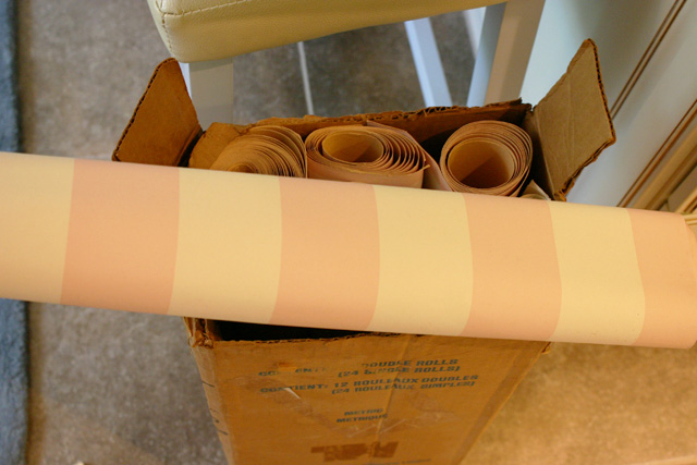 pink and white striped wallpaper rolls in box